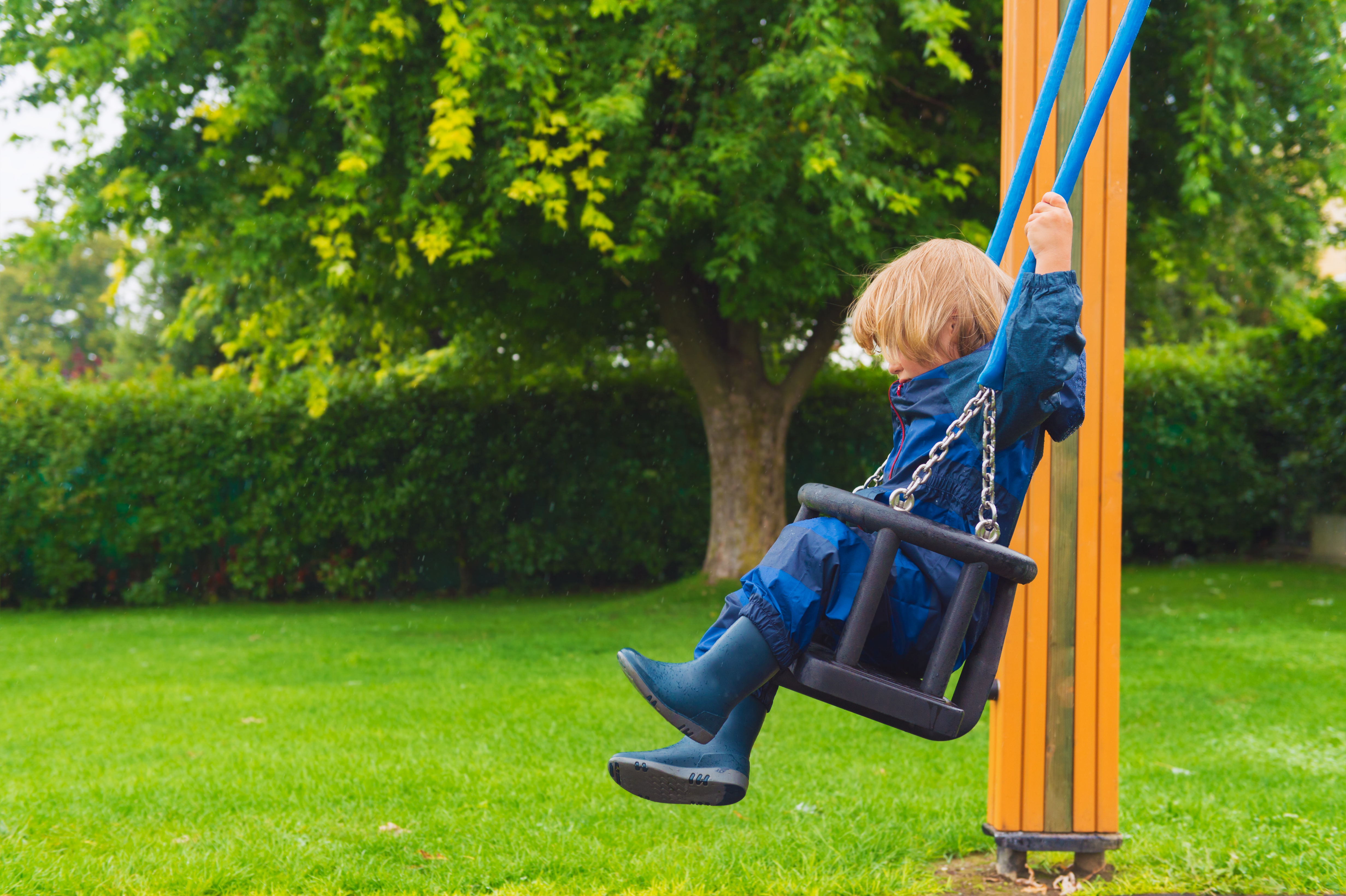 Cute little boy having fun on a swing on a rainy day, wearing blue waterpoof all-in-one suit